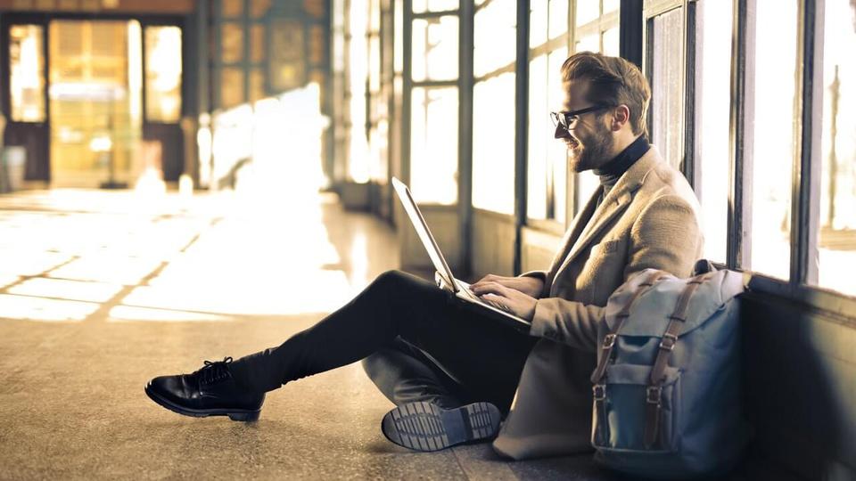 Processo seletivo Prefeitura de Uruguaiana: a imagem mostra homem sentado no chão mexendo em notebook com mochila ao lado