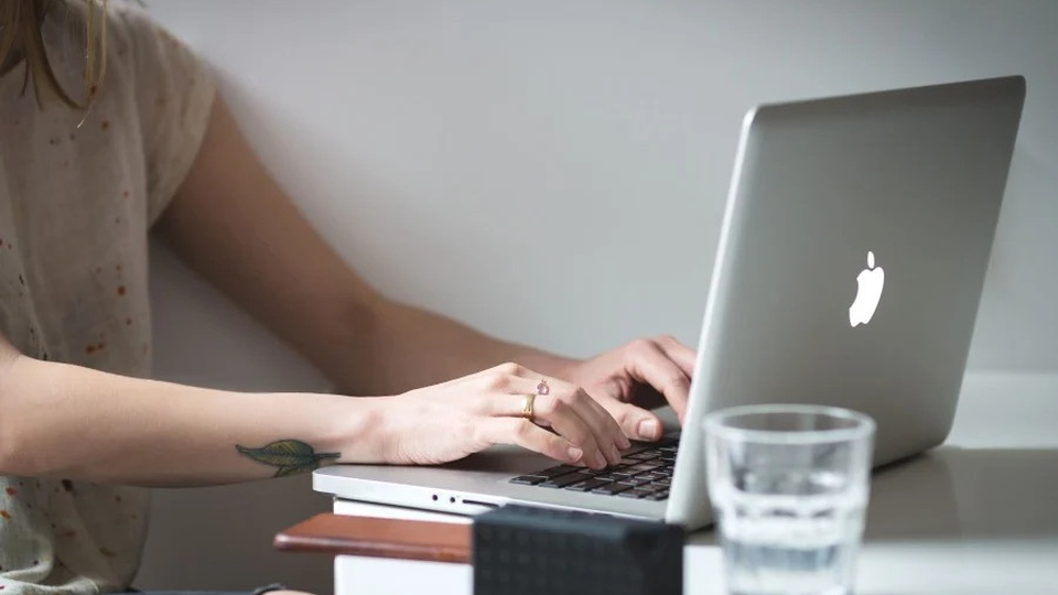 Processo seletivo Prefeitura de Vargem Bonita: a imagem mostra uma mulher branca, loira, com um dos braços tatuado, digitando em teclado de notebook da Apple