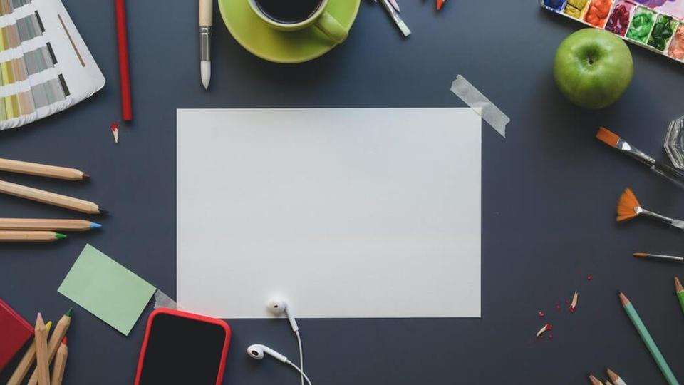 Processo seletivo Prefeitura de Várzea Paulista SP: a foto mostra uma mesa com bloco de anotações, fone, celular, café, canetas, lápis e outros objetos de desenhar