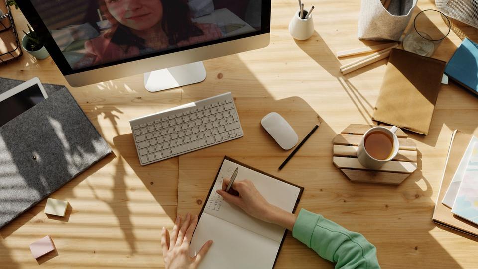 Processo seletivo Prefeitura de Victor Graeff: mesa de escritório com computador. Pessoa anotando algo em caderno com xícara de café à direita e post-its à esquerda