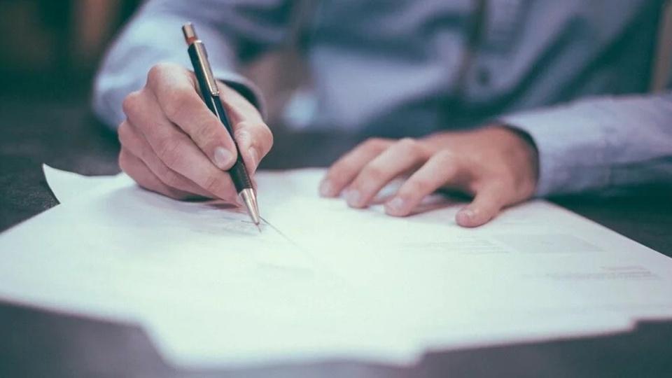 Processo seletivo Prefeitura Jardim de Piranhas - RN: na imagem, uma pessoa está segurando uma caneta e escrevendo em uma folha.