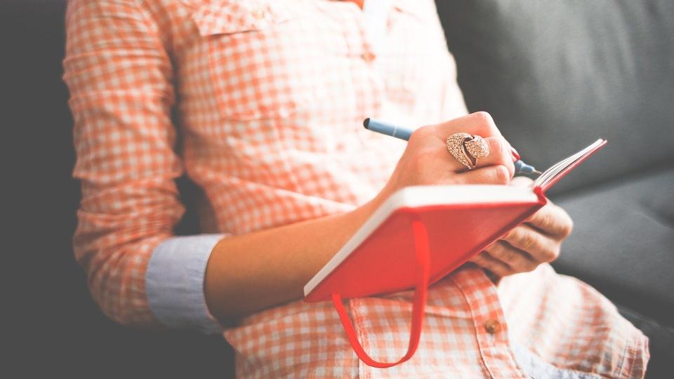 Processo seletivo Prefeitura Três Cachoeiras - RS: foco em mão feminina escrevendo em caderno