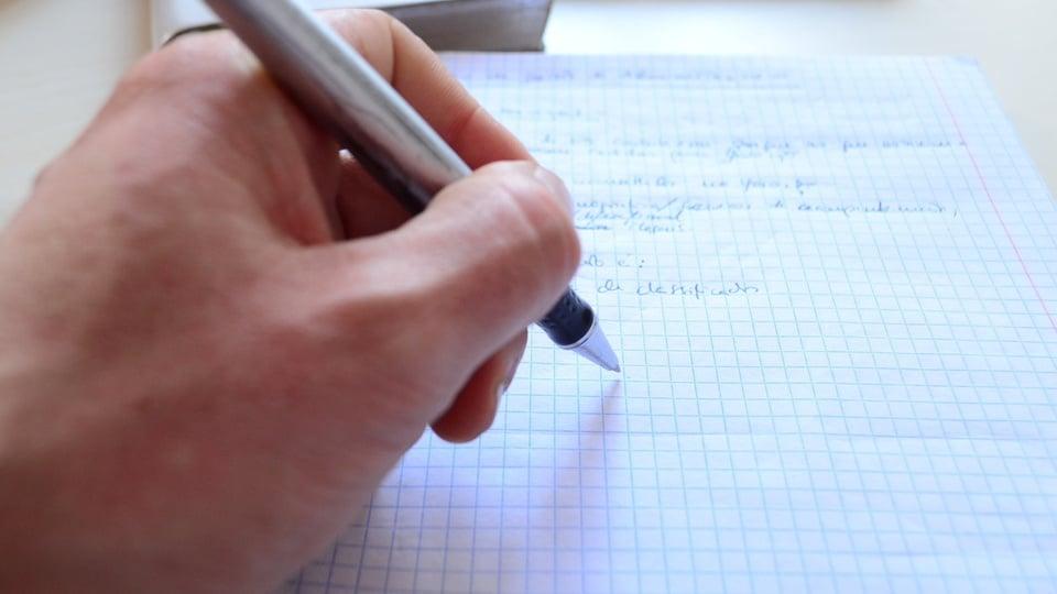 Processo seletivo SAMAE de Tijucas - SC: foco em mãos escrevendo em folha de papel