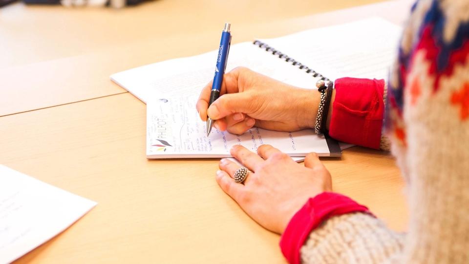 Processo seletivo Santa Gertrudes:  a imagem mostra pessoa escrevendo algo em bloco de papel sobre caderno