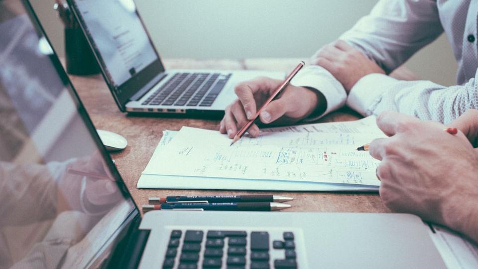 Processo seletivo São Pedro de Alcântara: a foto mostra pessoa com caneta na mão, fazendo anotações, uma mesa com dois notebooks e duas lapiseiras de grafite