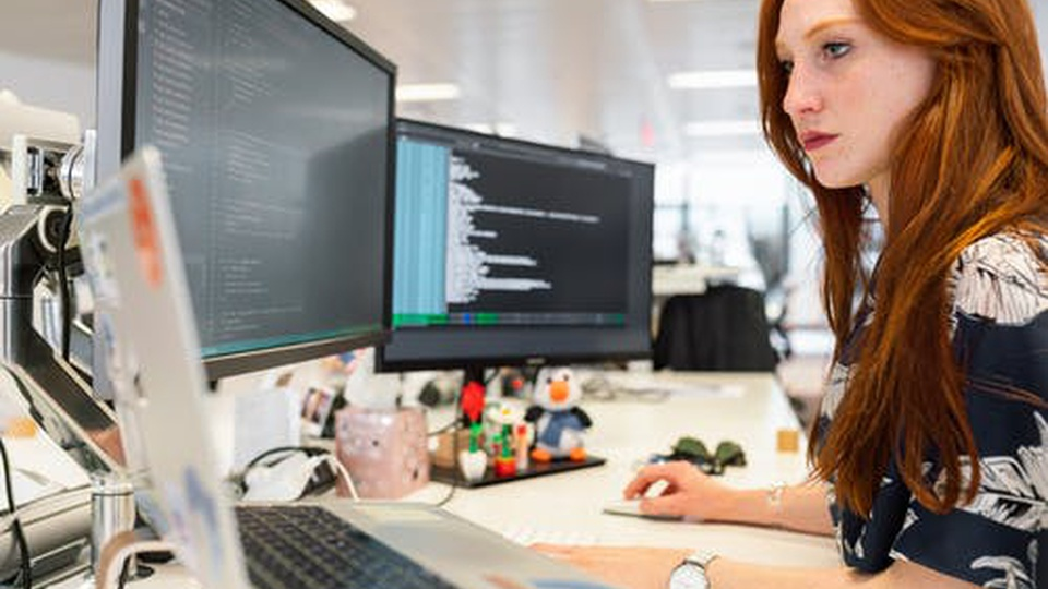 Processo Seletivo SEAD - GO: mulher com os braços sob mesa; utilizando computadores.
