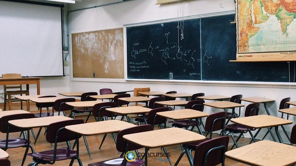 Processo seletivo SEE DF: a foto mostra uma sala de aula com carteiras, quadro verde de giz, tela branca de projeção e parte de um mapa na parede