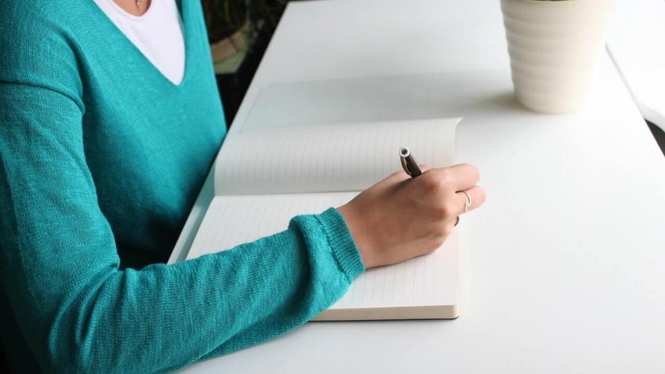 processo seletivo SEED PR: a imagem mostra pessoa escrevendo algo em papel sentada em escrivaninha