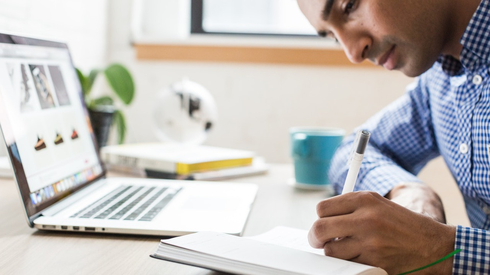 Processo seletivo SEFAZ MT: homem anotando algo num caderno em frente a um notebook aberto