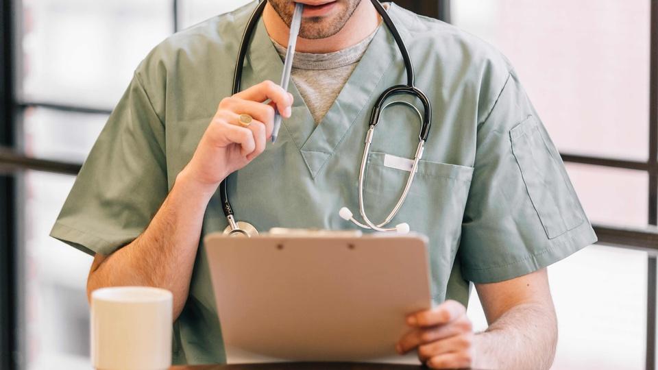 Processo seletivo SESPA: a foto mostra um profissional da saúde (homem) segurando uma prancheta, com o estetoscópio no pescoço e segurando com a mão direita uma caneta que está com a ponta na boca dele