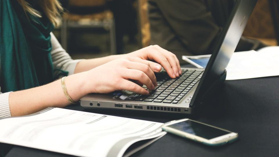 processo seletivo sop rs: a imagem mostra pessoa com as mãos no teclado do computador digitando algo com caderno aberto ao lado