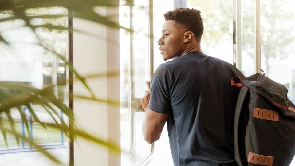 Programa de estágio na Ambev para estudantes negros: jovem negro, com mochila nas costas, saindo de um cômodo