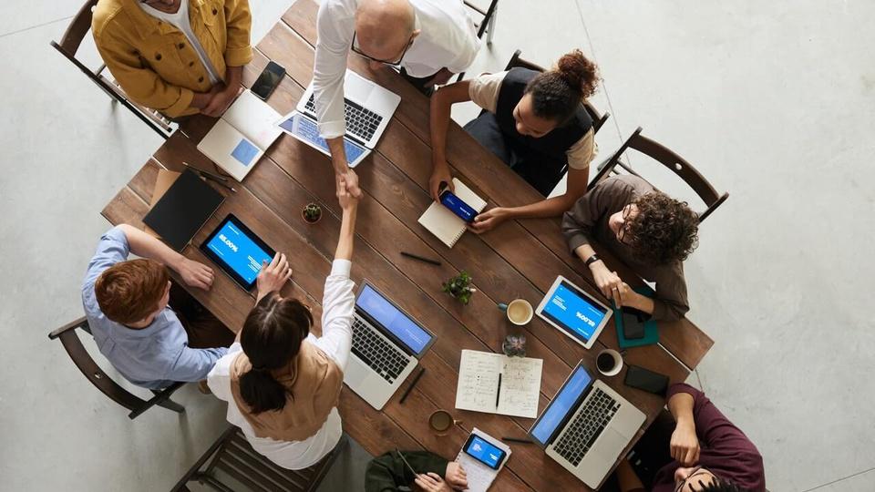 Programa Trainees Enforce: pessoas reunidas em uma mesa com seus tablets.