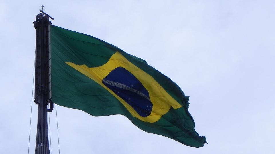 Programas sociais: bandeira do Brasil no alto do mastro balançando ao vento