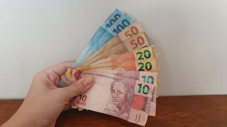 Projeto quer pagar abono salarial de R$ 1.045,00 aos brasileiros, mão segurando cédulas de dinheiro