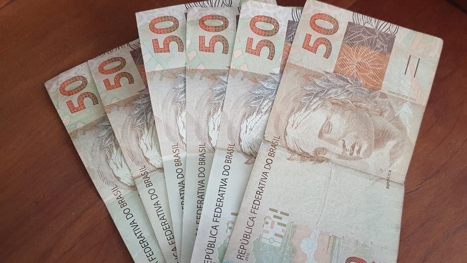 Auxílio de meio salário mínimo para informais: notas de cinquenta reais reunidas