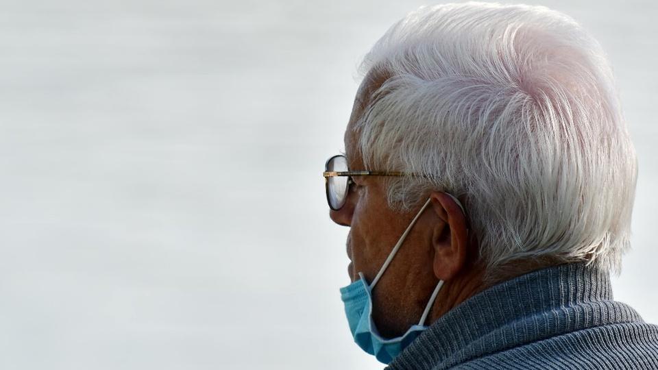programa emergencial para grupo de risco na pandemia: idoso olhando para o horizonte. Ele está com máscara hospitalar