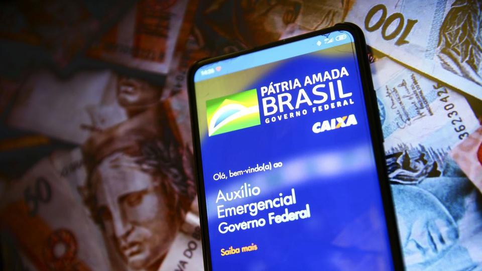 Auxílio emergencial de R$ 500 até dezembro: é possível ver tela de celular com página aberta do auxílio emergencial. No fundo, cédulas de dinheiro