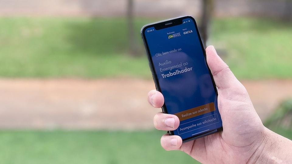 Prorrogação do auxílio emergencial por seis meses: mão segurando celular. Na tela, é possível ver a página inicial do auxílio emergencial