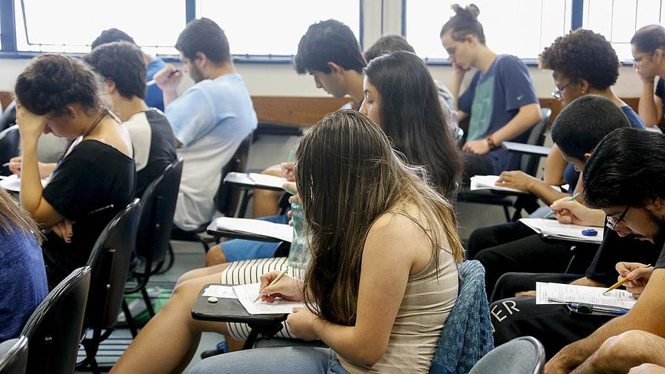 concursos públicos de 2021 para ensino médio: a imagem mostra várias pessoas sentadas numa sala de aula respondendo provas