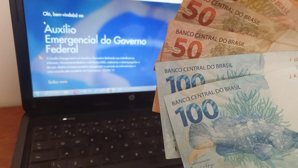 Auxílio emergencial: imagem mostra notas de 50 e 100 reais na lateral com computador aberto no site do auxilio emergencial ao fundo