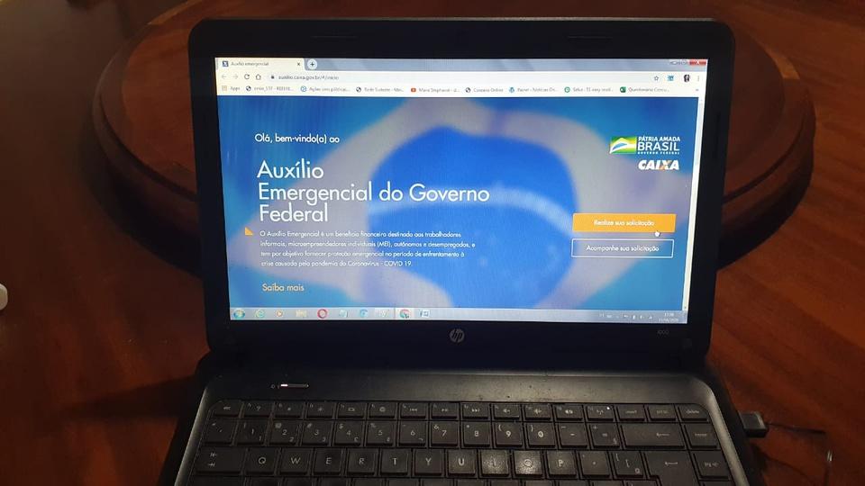 auxílio emergencial bolsa família: a imagem mostra computador aberto no site do auxílio emergencial