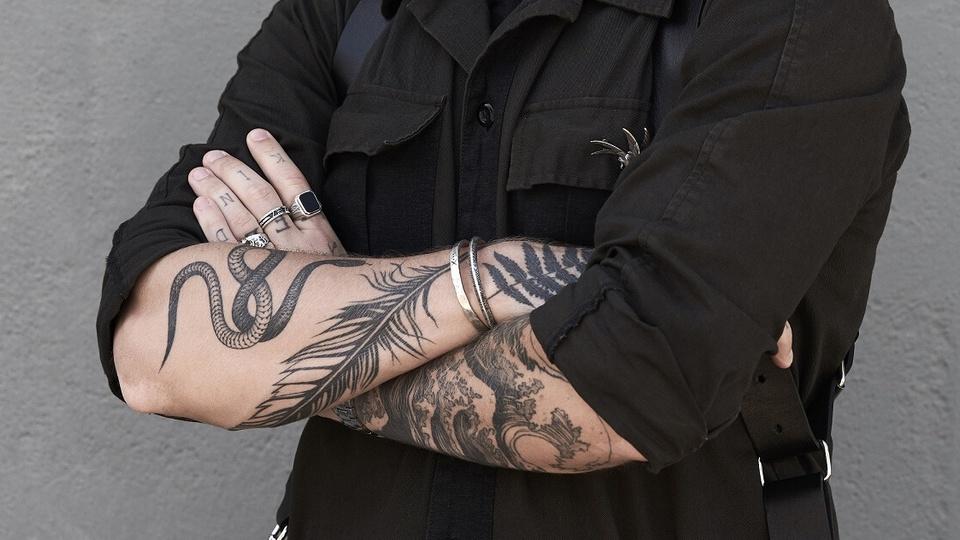 Quem tem tatuagens pode participar de concurso: homem vestido de preto com os braços cruzados cheios de tatuagem
