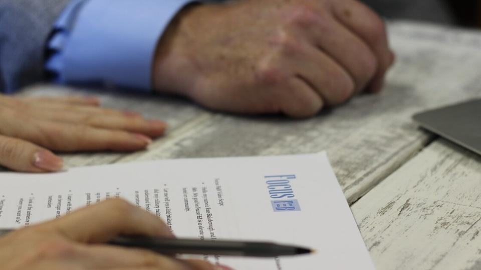 Retomada do projeto Carteira Verde e Amarela: enquadramento fechado em pessoa segurando uma caneta, com mãos apoiadas em mesa. Também é possível ver um papel disposto na mesma mesa