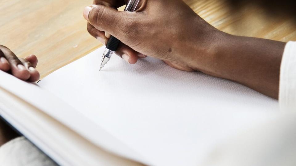 Processo seletivo SAAE de Ibiraçu - ES; pessoa escreve num papel com uma caneta