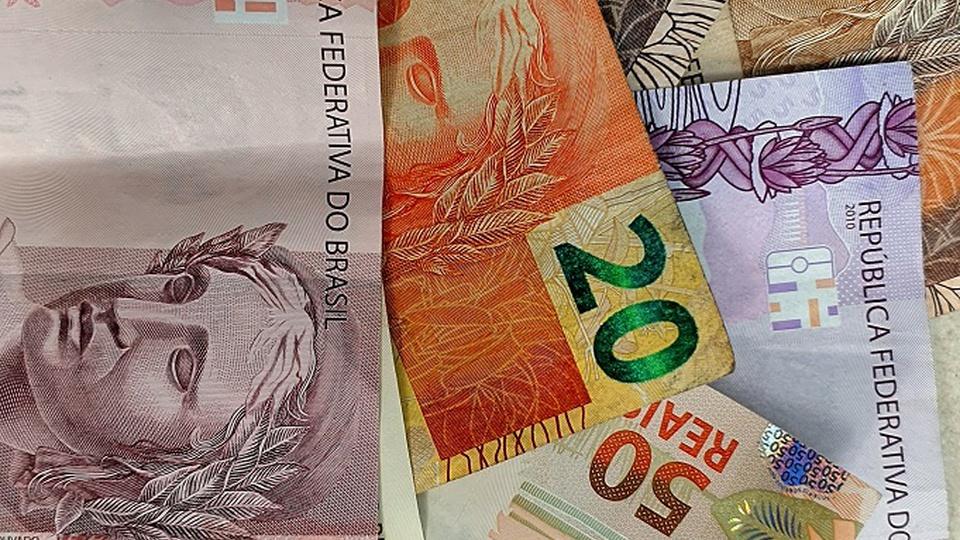 salário mínimo: a imagem mostra várias notas de dinheiro espalhadas