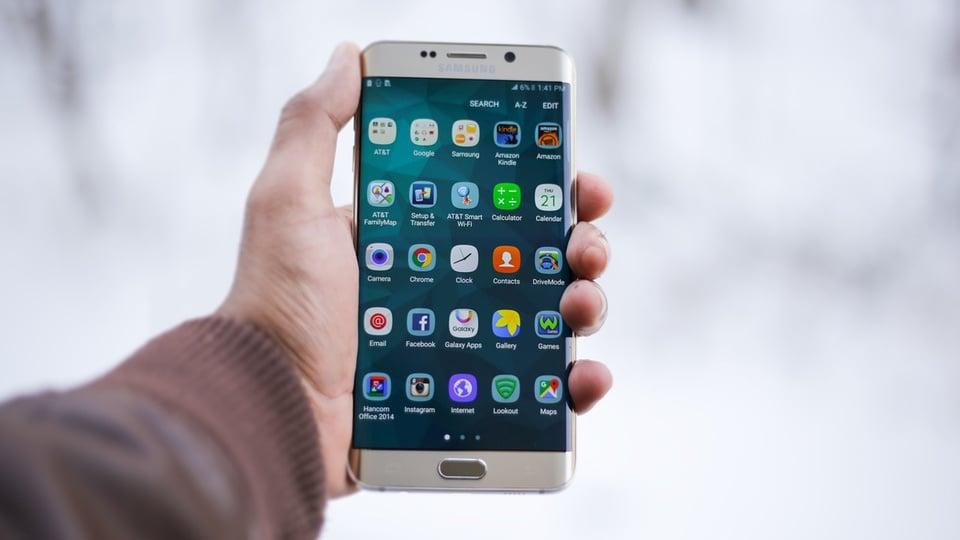 Samsung Money é anunciado e tem cartão de débito virtual, mão segurando celular da Samsung