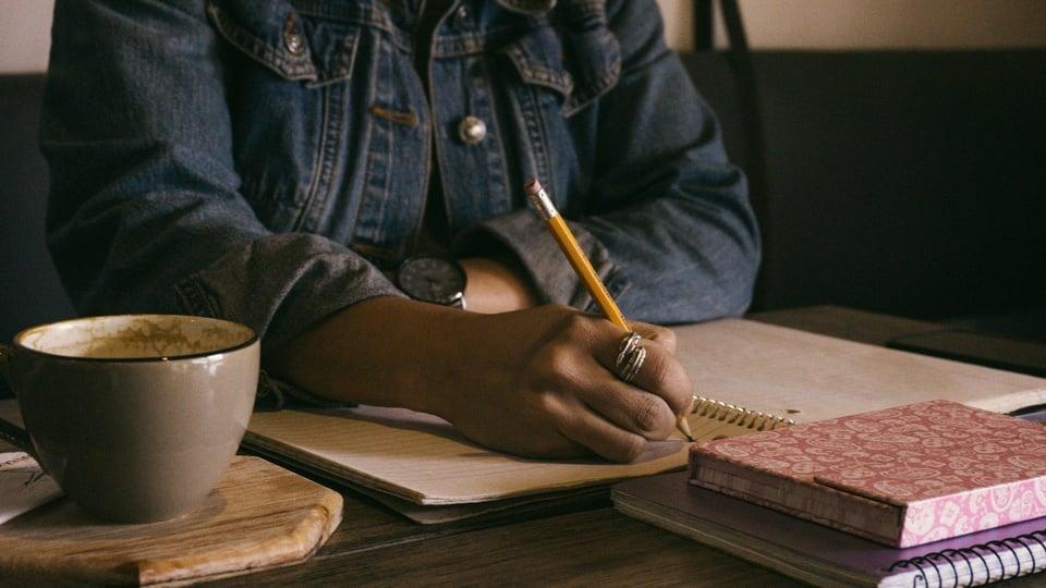 Prefeitura de São Martinho: pessoa fazendo anotações. Ela está usando uma jaqueta jeans e segurando um lápis. Na mesa há cadernos e uma xícara.