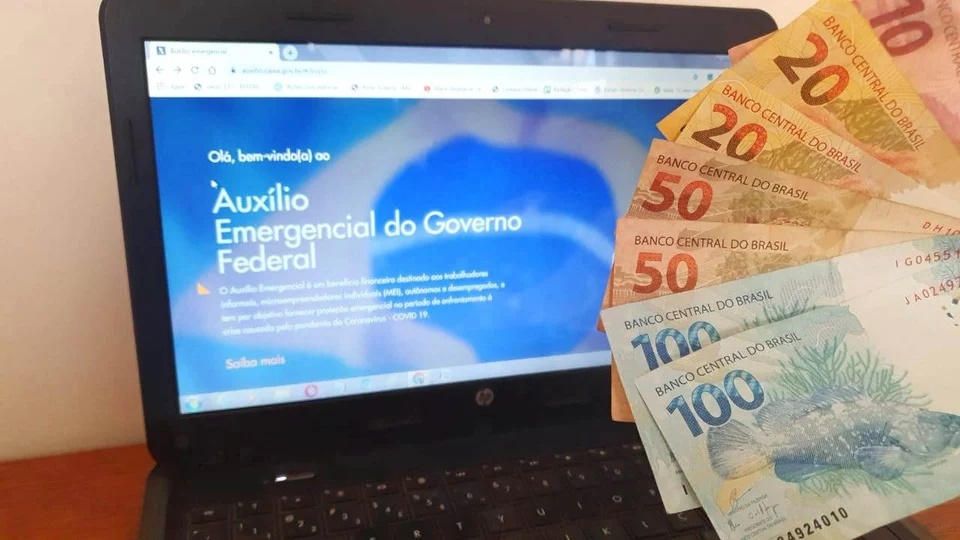 Saque do auxílio emergencial 2021: mão segurando dinheiro. No fundo, é possível ver tela de computador com página do auxílio emergencial aberta
