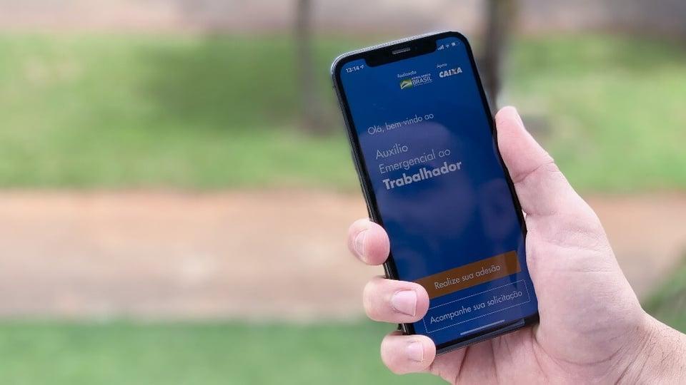 Saque em dinheiro do auxílio emergencial: pessoa segurando o celular com o aplicativo do auxílio emergencial na tela