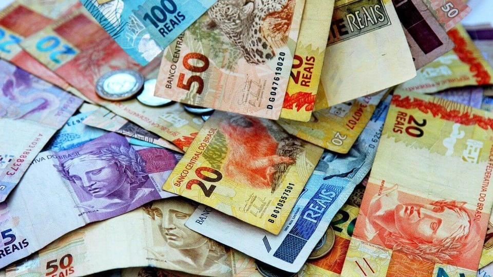 saque integral do fgts: a imagem mostra várias notas de dinheiro e moedas espalhadas