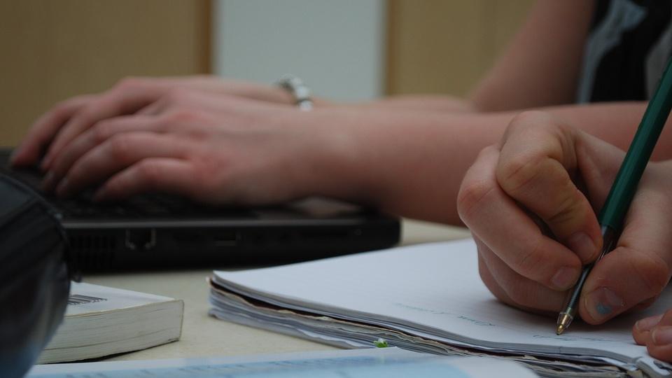 Processo seletivo SEAD - SE: foco em mão escrevendo em folha de papel; ao fundo pessoa digitando em teclado de notebook