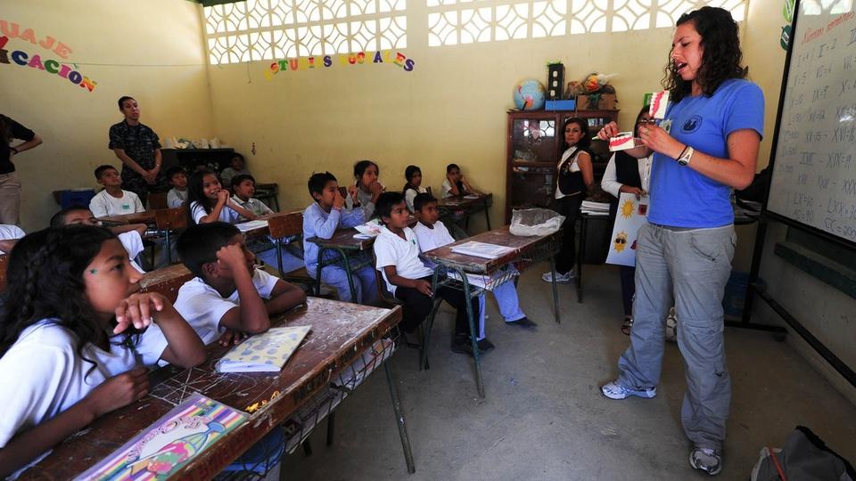 SEDUC - MA abre processo seletivo: professor explicando assunto a grupo de crianças em sala de aula