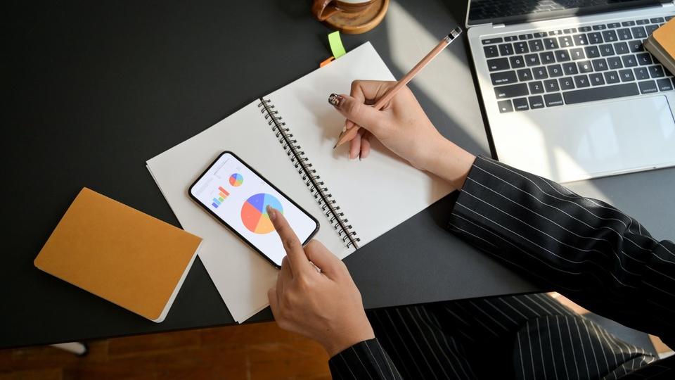 Hábitos matinais: mulher anotando algo em caderno e apontando o dedo para o celular. Ao seu lado esquerdo um bloquinho fechado e ao lado direito um notebook aberto
