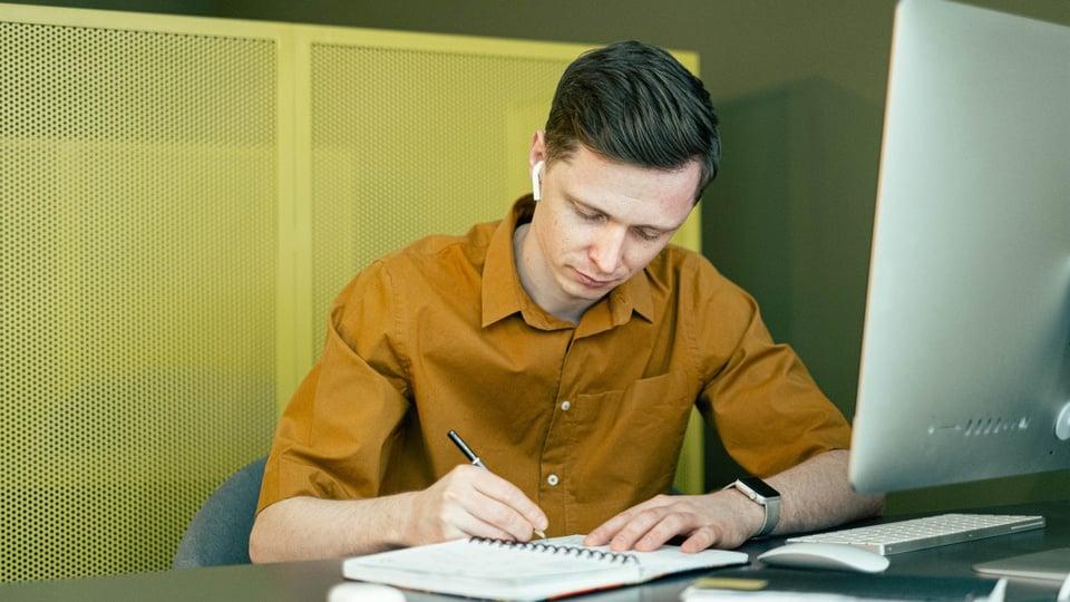 Processo seletivo Prefeitura de São Pedro do Sul - RS; homem escrevendo em um caderno em frente a um computador