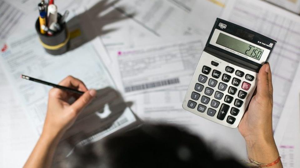 Número de famílias endividadas em 2021: enquadramento em mão segurando calculadora. No fundo, é possível ver papéis dispostos em superfície plana