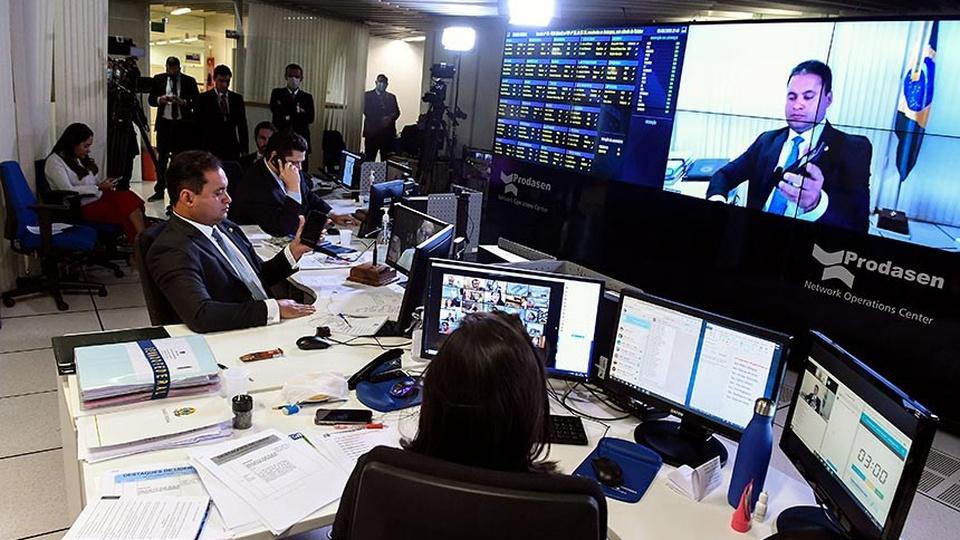 Senado aprova congelamento de salários; possível impacto em concursos: escritório com funcionários, computadores, papéis e uma grande tela