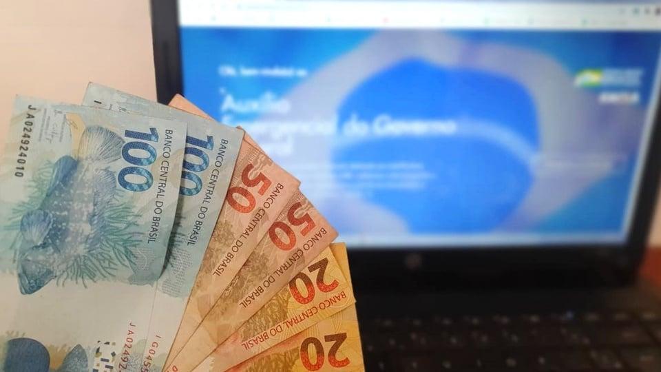 auxílio emergencial até dezembro: leque de dinheiro em frente computador