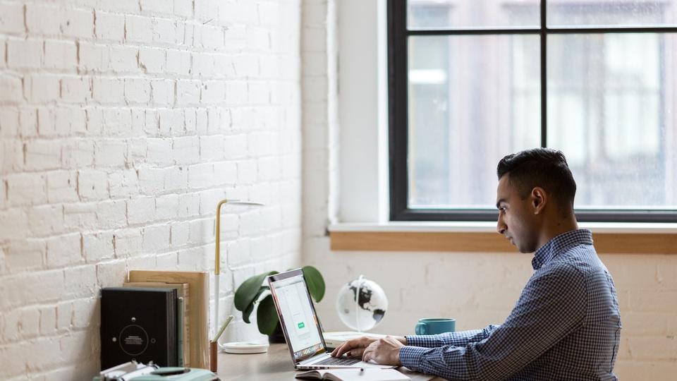 SENAI abre cursos de capacitação profissional gratuitos: homem sentado em escrivaninha mexendo no computador