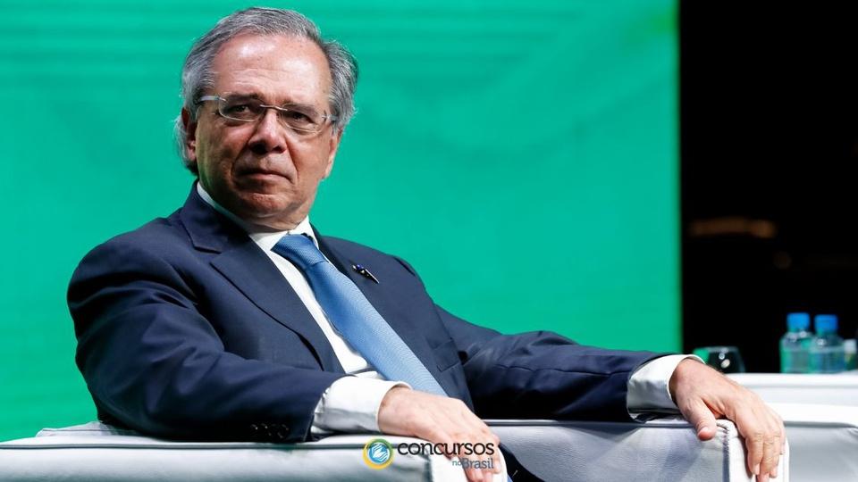 Ministro da Economia Paulo Guedes: com terno e gravata azul escuro sentado e olhando para o lado usando óculos