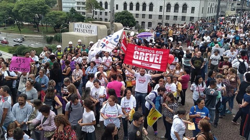 greve servidor desconto: a imagem mostra várias pessoas na rua com cartazes