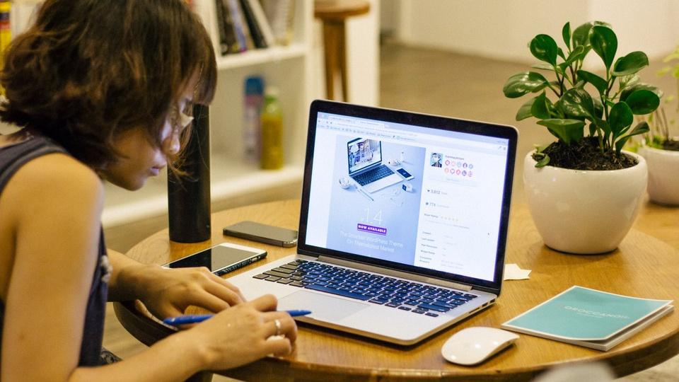 SES SP: mulher mexendo no computador segurando caneta. No lado esquerdo há um celular apoiado sobre a mesa e no lado esquerdo tem o mouse sem fio e um livrinho