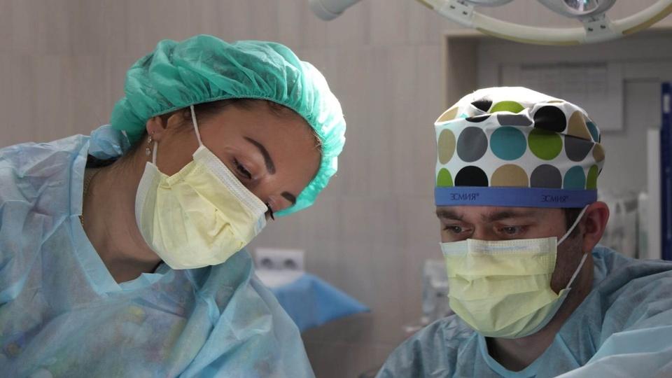 Processo seletivo SESAU - RO: #PraCegoVer dois profissionais da saúde em sala de operação; busto para cima. Ambos estão com máscara hospitalar e vestimenta padrão na cor azul.