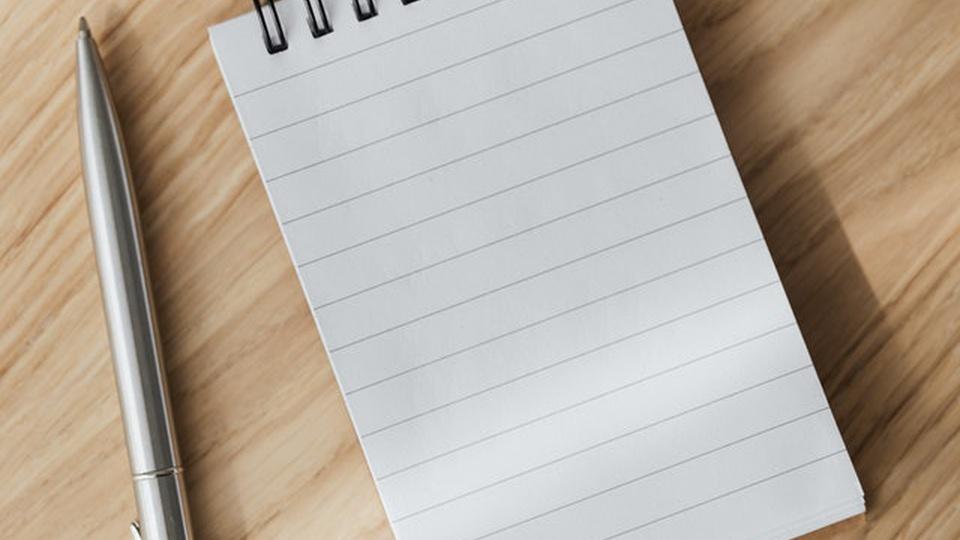 SINFRA MT: sobre uma mesma há uma caneta e um bloco de anotações