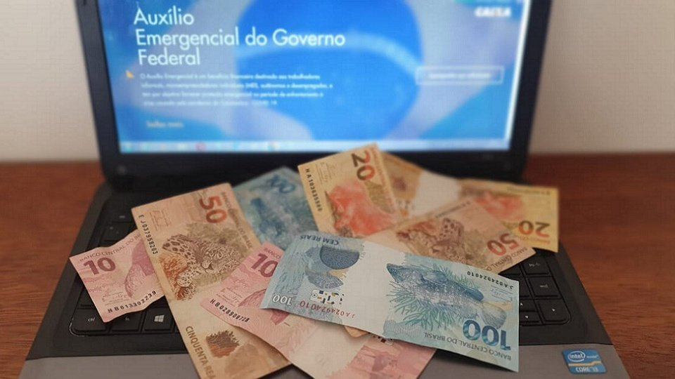 excluídos do auxílio emergencial: notas de dinheiro jogadas em cima do notebook aberto no site do auxílio emergencial