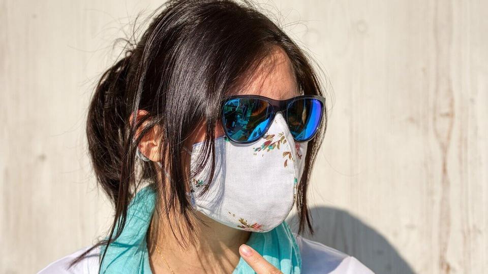 Trabalhador infectado pelo coronavírus: mulher de cabelo preso usando máscara cirúrgica de pano e óculos escuros